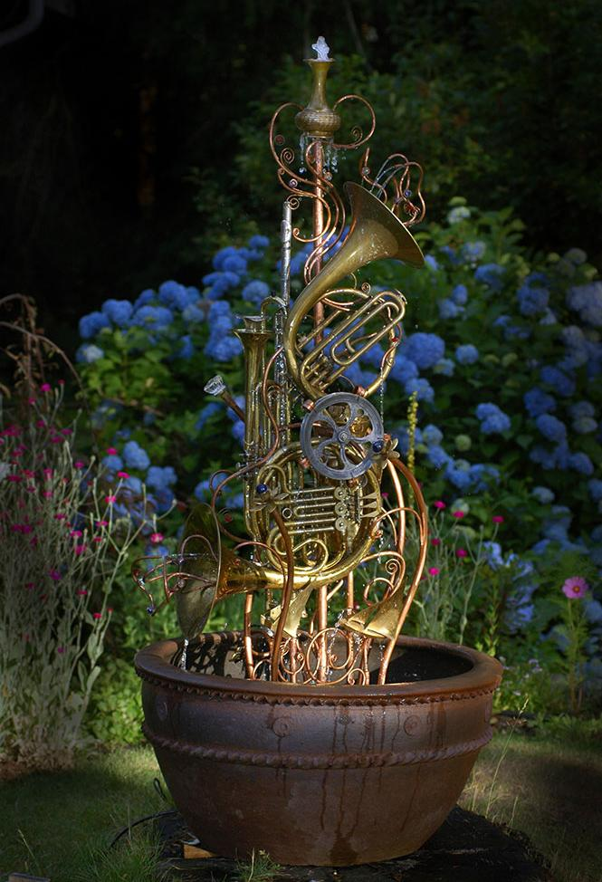 Musical instrument fountain sculpture consisting of copper tubing, a water wheel, upcycled french horns, flutes, trumpets, and brass and silver collectibles.