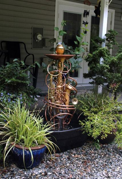 Musical instrument fountain sculpture consisting of copper tubing, a water wheel, brass and silver collectables, and upcycled musical instruments including saxes and trumpets.