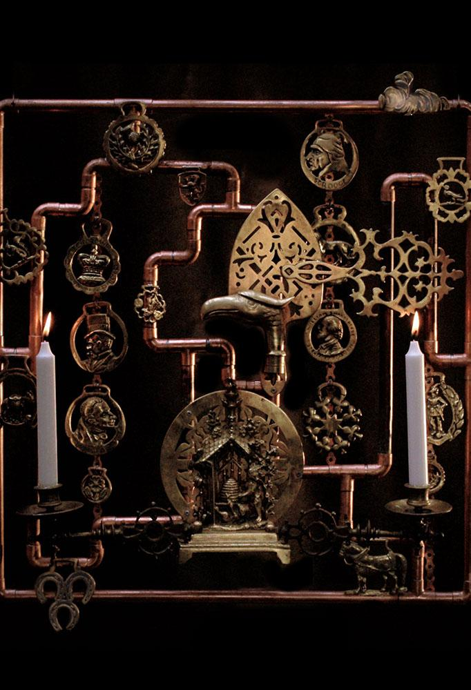 Made from a collection of mostly brass pieces mounted on a copper tube structure.